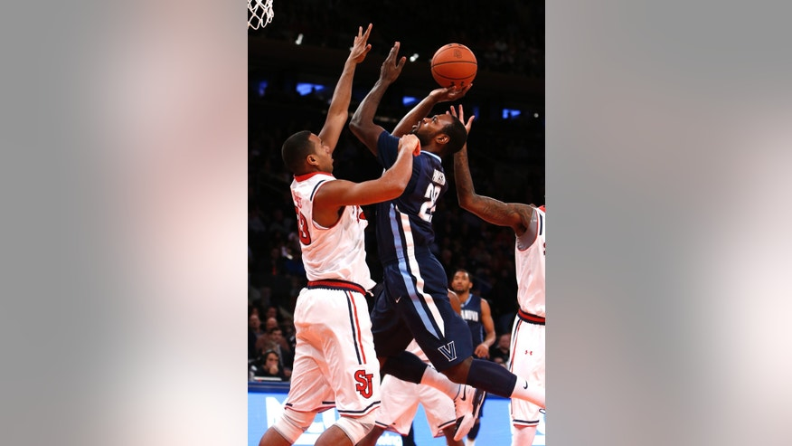 Villanova's JayVaughn Pinkston (22) goes to the basket against St. John's Orlando Sanchez, left, of the Dominican Republic, during the first half of an NCAA college basketball game Saturday, Jan. 11, 2014, in New York. (AP Photo/Jason DeCrow)