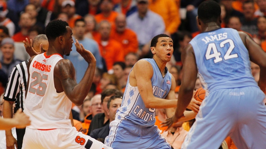 North Carolina's Marcus Paige, center, looks to pass the ball to Joel James, right, while under pressure from Syracuse's Rakeem Christmas, left, in the second half of an NCAA college basketball game in Syracuse, N.Y., Saturday, Jan. 11, 2014. Syracuse won 57-45. (AP Photo/Nick Lisi)