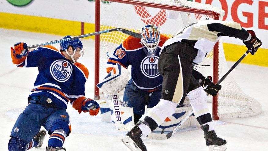 Pittsburgh Penguins' Taylor Pyatt (17) is stopped by Edmonton Oilers goalie Devan Dubnyk (40) as Martin Marincin, left, tries to defend during the second period of an NHL hockey game Friday, Jan. 10, 2014, in Edmonton, Alberta. (AP Photo/The Canadian Press, Jason Franson)