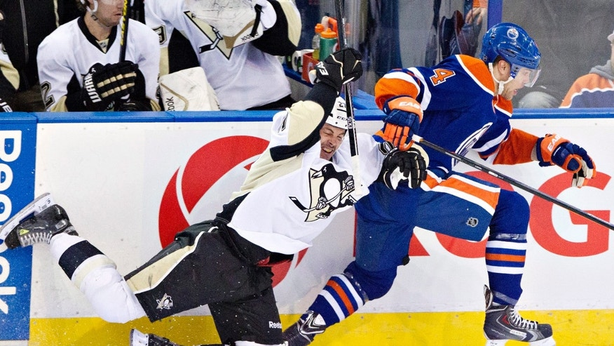 Pittsburgh Penguins' Craig Adams (27) is checked by Edmonton Oilers' Taylor Hall (4) during first-period NHL hockey game action in Edmonton, Alberta, Friday, Jan. 10, 2014. (AP Photo/The Canadian Press, Jason Franson)