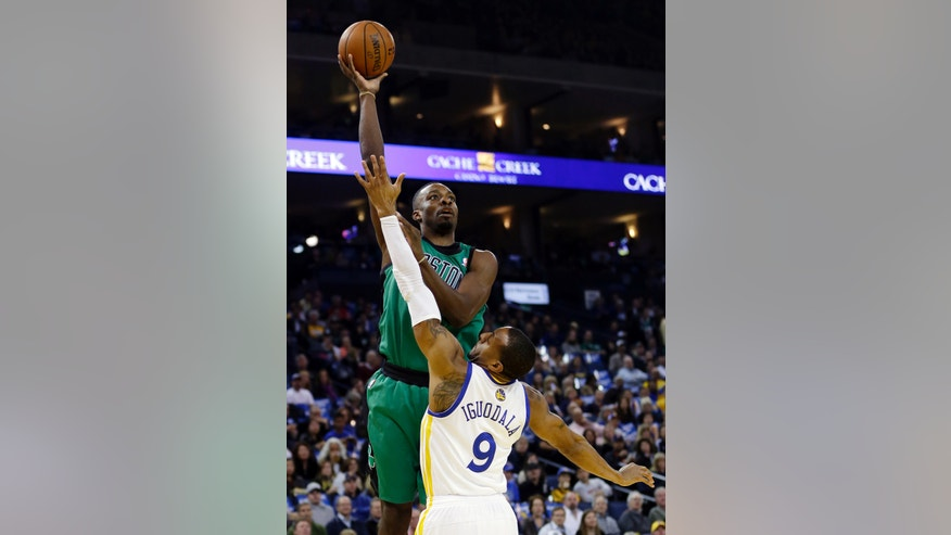 Boston Celtics' Jeff Green, top, shoots over Golden State Warriors' Andre Iguodala (9) during the first half of an NBA basketball game Friday, Jan. 10, 2014, in Oakland, Calif. (AP Photo/Marcio Jose Sanchez)