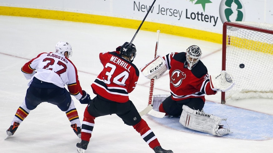 Florida Panthers' Nick Bjugstad (27) shots the puck past New Jersey Devils' Jon Merrill (34) and goalie Cory Schneider (35) for a goal during the second period of an NHL hockey game in Newark, N.J., Saturday, Jan. 11, 2014. (AP Photo/Rich Schultz)