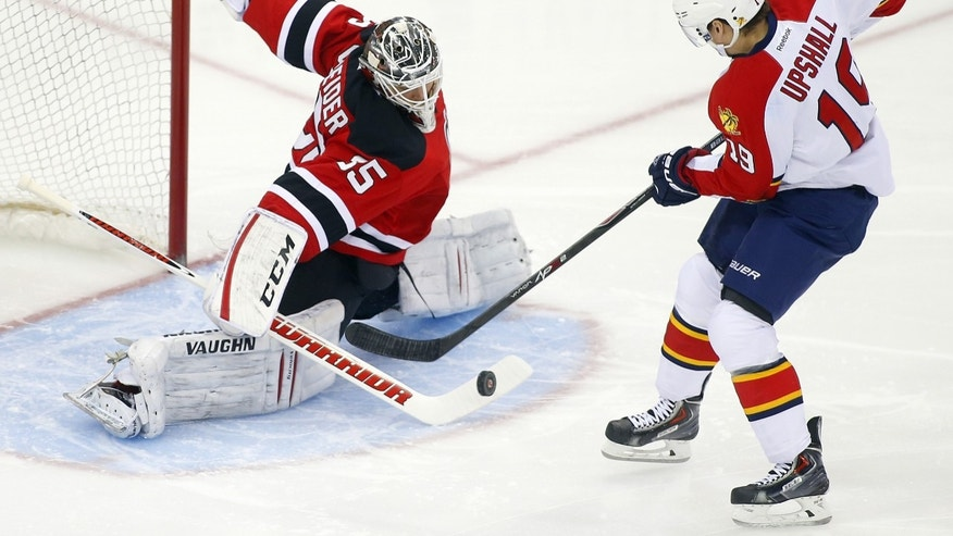 New Jersey Devils goalie Cory Schneider (35) makes a save on a shot by Florida Panthers' Scottie Upshall (19) during the first period of an NHL hockey game in Newark, N.J., Saturday, Jan. 11, 2014. (AP Photo/Rich Schultz)