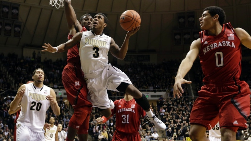 Purdue guard Ronnie Johnson (3) is fouled as he shoots between Nebraska forward Leslee Smith, left, and guard Tai Webster in the second half of an NCAA college basketball game in West Lafayette, Ind., Sunday, Jan. 12, 2014. Purdue defeated Nebraska 70-64. (AP Photo/Michael Conroy)