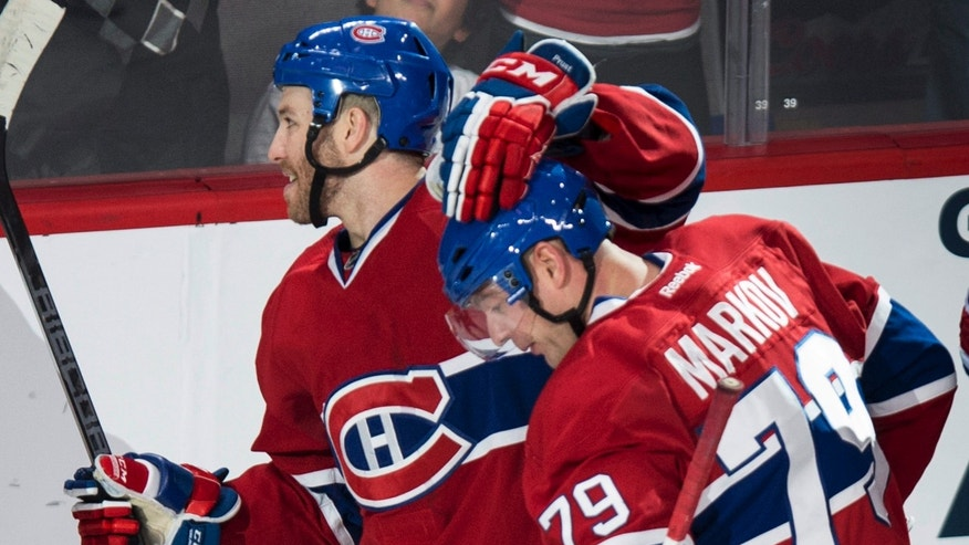 Montreal Canadiens' Andrei Markov is congratulated by teammate Brandon Prust following a goal against the Chicago Blackhawks during the second period of an NHL hockey game Saturday, Jan. 11, 2014, in Montreal. The Canadiens won 2-1 in overtime. (AP Photo/The Canadian Press, Paul Chiasson)