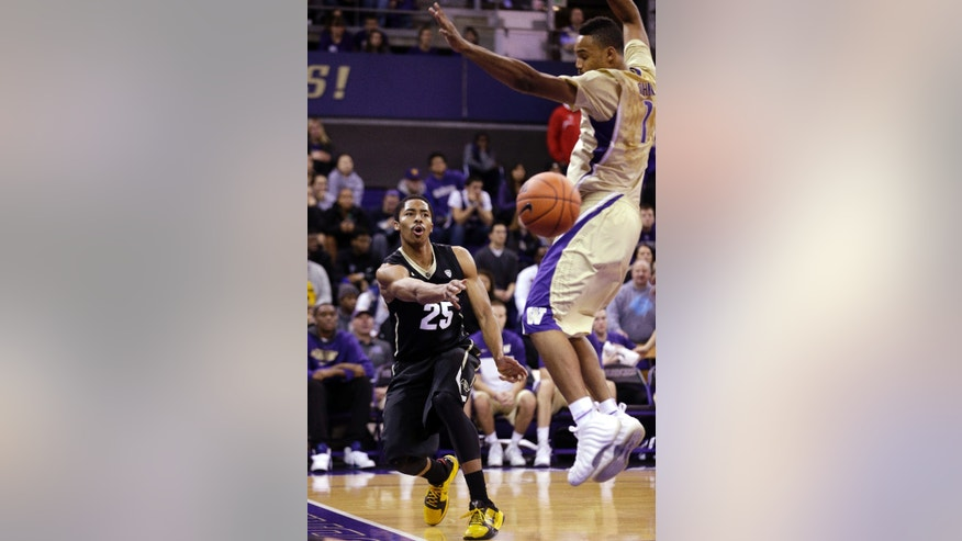 Colorado's Spencer Dinwiddie (25) puts a baseline pass by Washington's Darin Johnson in the first half of an NCAA men's basketball game Sunday, Jan. 12, 2014, in Seattle. (AP Photo/Elaine Thompson)