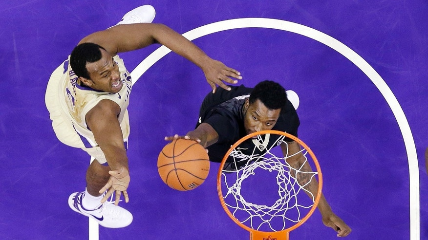 Colorado's Wesley Gordon, right, knocks away a shot by Washington's Perris Blackwell in the first half of an NCAA college basketball game on Sunday, Jan. 12, 2014, in Seattle. (AP Photo/Elaine Thompson)