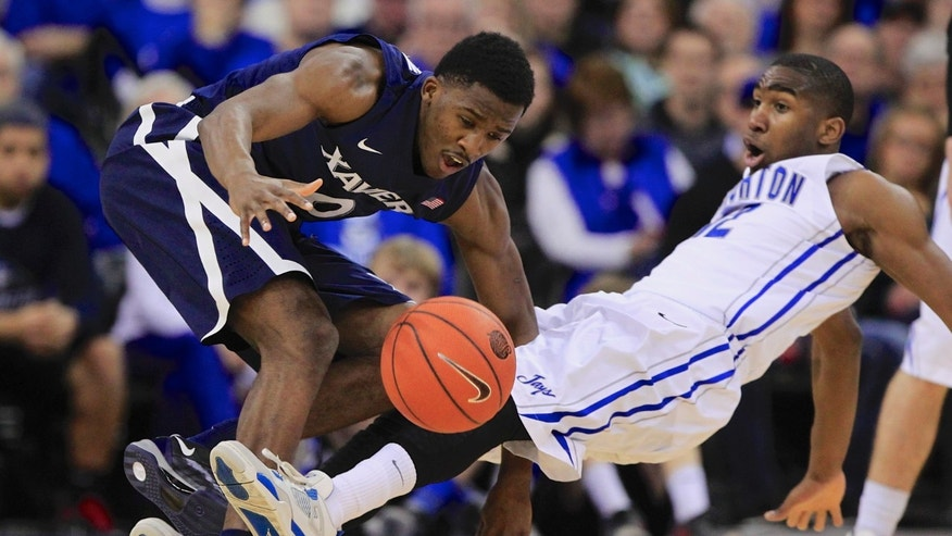 Xavier's Semaj Christon (0) fouls Creighton's Jahenns Manigat (12) in the first half of an NCAA college basketball game in Omaha, Neb., Sunday, Jan. 12, 2014. (AP Photo/Nati Harnik)