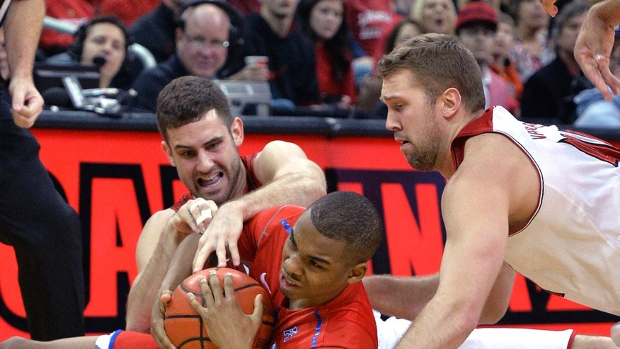 Louisville's Luke Hancock, left, and Stephan Van Treese, right, battle SMU's Ben Moore for a loose ball during the first half of an NCAA college basketball game Saturday Jan. 12, 2014, in Louisville, Ky. (AP Photo/Timothy D. Easley)