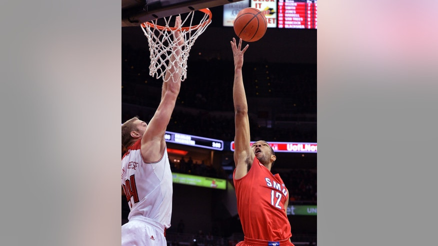 SMU's Nick Russell, right, attempts a layup over the defense of Louisville's Stephan Van Treese during the first half of an NCAA college basketball game Saturday, Jan. 12, 2014, in Louisville, Ky. (AP Photo/Timothy D. Easley)