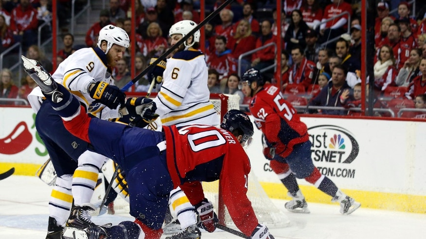 Buffalo Sabres center Steve Ott (9) checks Washington Capitals right wing Troy Brouwer (20) in the first period of an NHL hockey game on Sunday, Jan. 12, 2014, in Washington. (AP Photo/Alex Brandon)