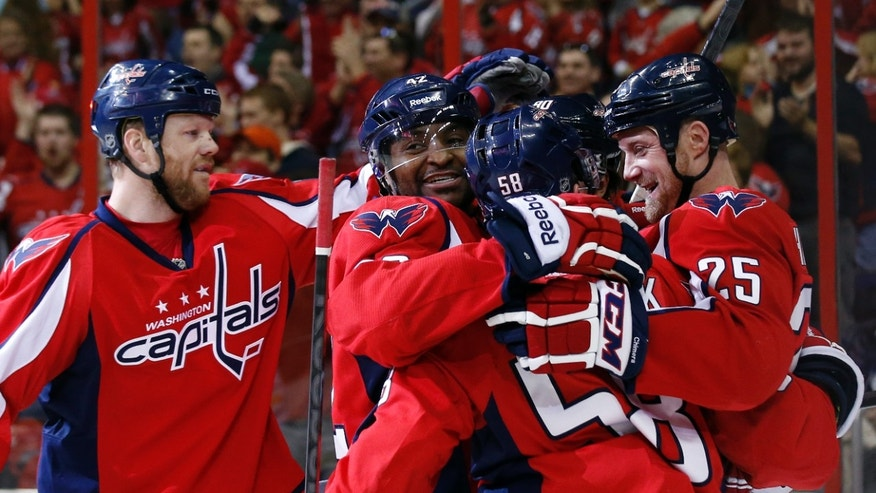 Washington Capitals left wing Jason Chimera (25) celebrates his goal with teammates in the first period of an NHL hockey game against the Buffalo Sabres, Sunday, Jan. 12, 2014, in Washington. (AP Photo/Alex Brandon)