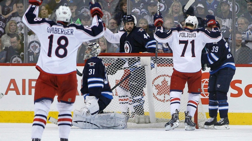 Columbus Blue Jackets' Nick Foligno (71) and RJ Umberger (18) celebrate Foligno's goal against the Winnipeg Jets goaltender Ondrej Pavelec (31), Zach Bogosian (44) and Tobias Enstrom (39) during second period of an NHL hockey game in Winnipeg, Manitoba, on Saturday, Jan. 11, 2014. (AP Photo/The Canadian Press, John Woods)