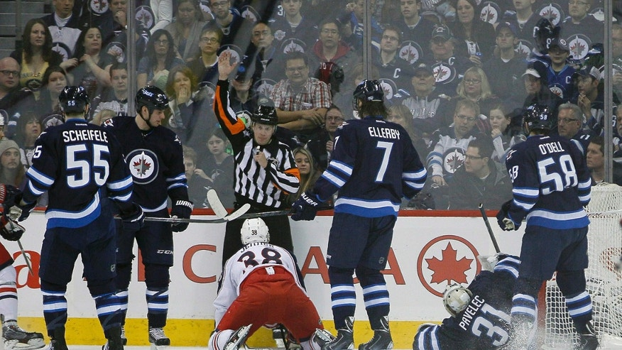 The referee calls a penalty shot on the Winnipeg Jets after Adam Pardy (2) hauled down Columbus Blue Jackets' Boone Jenner (38) during second period of an NHL hockey game in Winnipeg, Manitoba, on Saturday, Jan. 11, 2014. (AP Photo/The Canadian Press, John Woods)