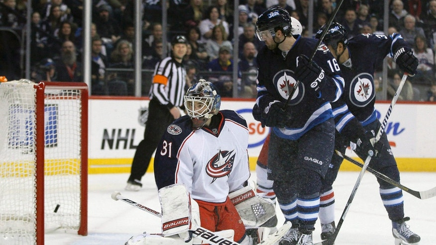Columbus Blue Jackets goaltender Curtis McElhinney (31) and Winnipeg Jets' Andrew Ladd (16) watch as Jets' Tobias Enstrom's (39) shot from the point goes in during second period of an NHL hockey game in Winnipeg, Manitoba, on Saturday, Jan. 11, 2014. (AP Photo/The Canadian Press, John Woods)