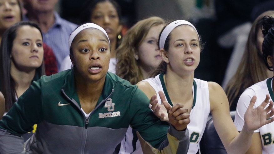Baylor guard Odyssey Sims, left, and teammate Makenzie Robertson watch from the bench during the second half of an NCAA college basketball game against TCU, Saturday, Jan. 11, 2014, in Waco, Texas. Baylor won 80-46. (AP Photo/LM Otero)