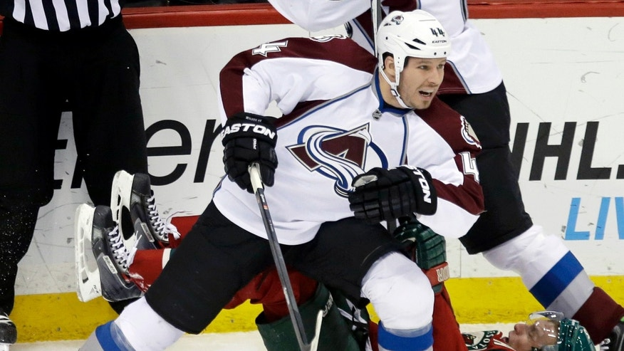 Colorado Avalanche's Ryan Wilson, left, leaves Minnesota Wild's Dany Heatley on the ice as he skates away after a collision in the first period of an NHL hockey game, Saturday, Jan. 11, 2014, in St. Paul, Minn. (AP Photo/Jim Mone)