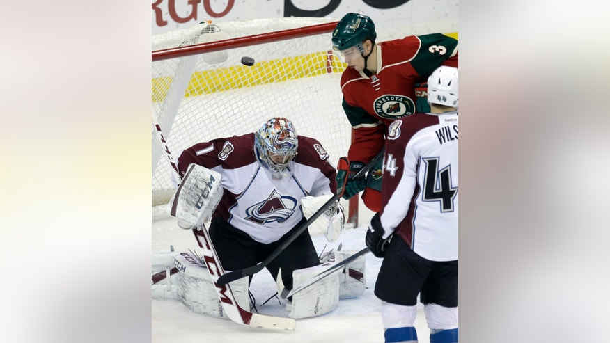 Minnesota Wild's Charlie Coyle (3) looks for the rebound as Colorado Avalanche goalie Semyon Varlamov, of Russia, defects a shot into the air in the first period of an NHL hockey game, Saturday, Jan. 11, 2014, in St. Paul, Minn. (AP Photo/Jim Mone)