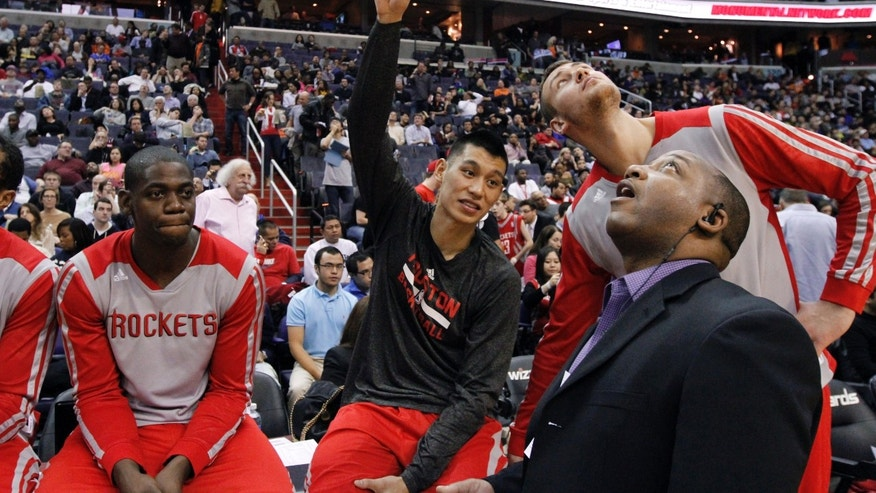 Houston Rockets forward Ronnie Brewer, left, guard Jeremy Lin and forward Donatas Motiejunas, from Lithuania, and Bryant Savage, director of security services for the Rockets, talk about the water leak in the ceiling that delayed the start of the second half of an NBA basketball game against the Washington Wizards, Saturday, Jan. 11, 2014, in Washington. The Rockets won 114-107. (AP Photo/Alex Brandon)