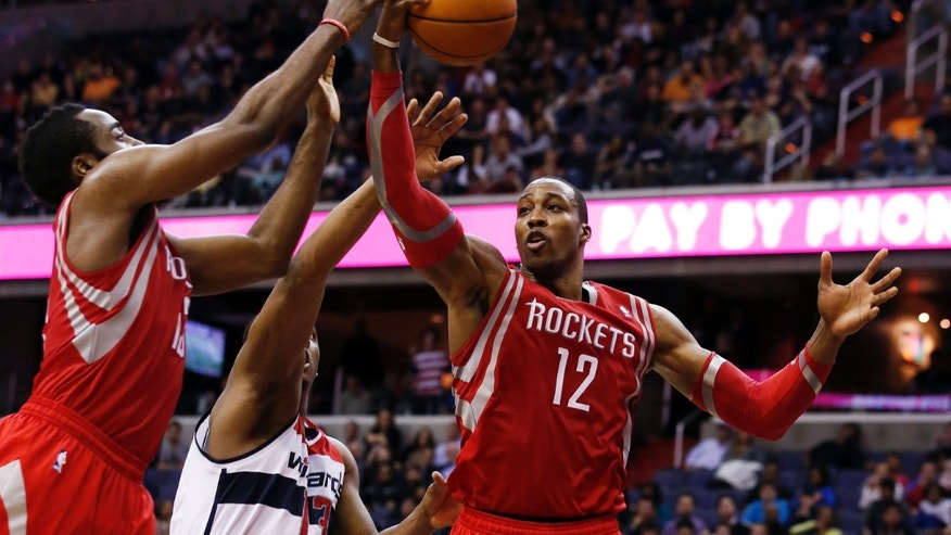 Houston Rockets forward Dwight Howard (12) grabs a rebound in front of Washington Wizards center Kevin Seraphin (13), from France, and Rockets' James Harden (13) during the second half of an NBA basketball game Saturday, Jan. 11, 2014, in Washington. The Rockets won 114-107. (AP Photo/Alex Brandon)
