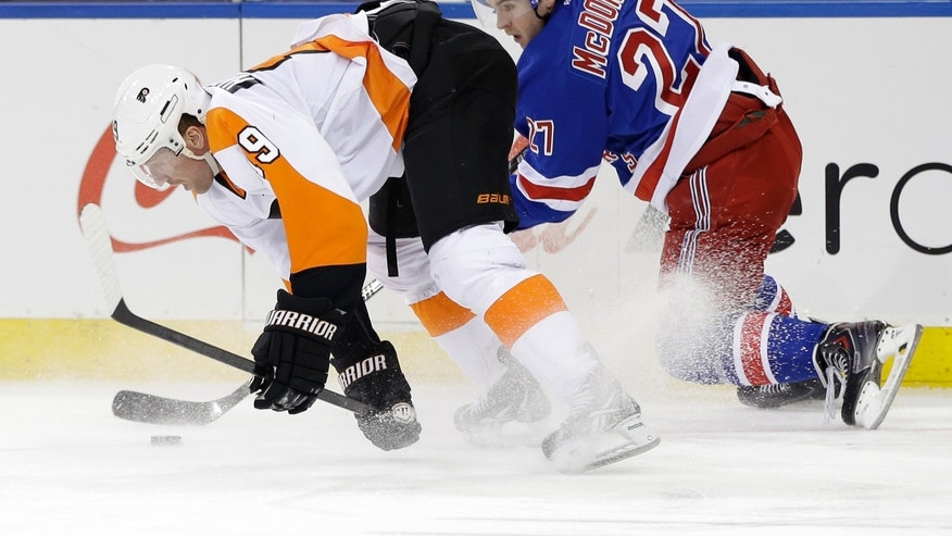 New York Rangers' Ryan McDonagh, right, and Philadelphia Flyers' Scott Hartnell scramble for the puck during the first period of the NHL hockey game, Sunday, Jan. 12, 2014, in New York. (AP Photo/Seth Wenig)