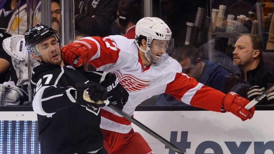 Detroit Red Wings right wing Patrick Eaves, right, and Los Angeles Kings defenseman Alec Martinez battle for the puck during the first period of an NHL hockey game, Saturday, Jan. 11, 2014, in Los Angeles. (AP Photo/Mark J. Terrill)