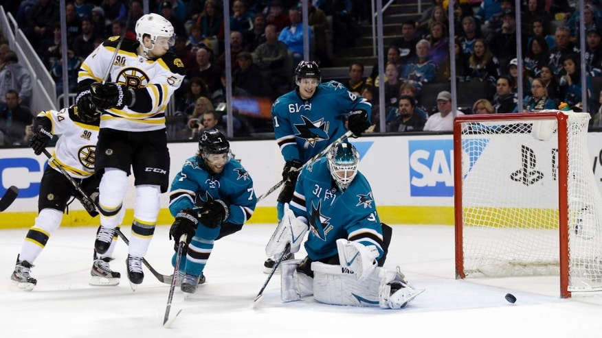 San Jose Sharks goalie Antti Niemi (31), of Finland, deflects a shot on goal next to Boston Bruins' Ryan Spooner, left, during the second period of an NHL hockey game on Saturday, Jan. 11, 2014, in San Jose, Calif. (AP Photo/Marcio Jose Sanchez)