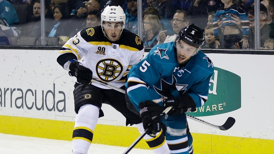 San Jose Sharks' Jason Demers (5) controls the puck next to Boston Bruins' Brad Marchand (63) during the second period of an NHL hockey game on Saturday, Jan. 11, 2014, in San Jose, Calif. (AP Photo/Marcio Jose Sanchez)