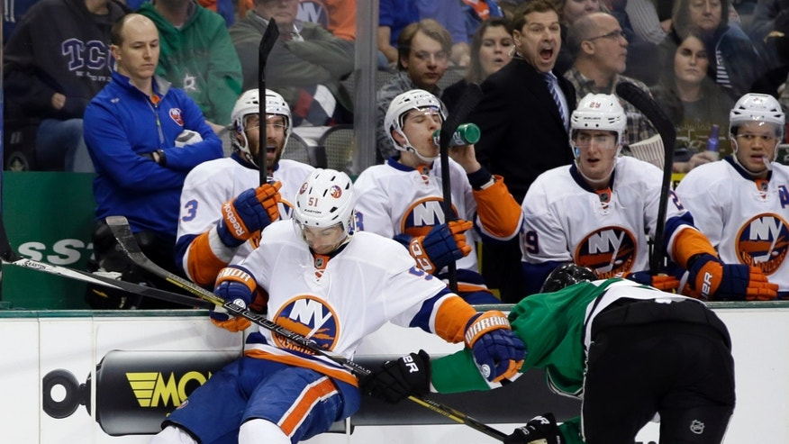 New York Islanders center Frans Nielsen, left, of Denmark, attempts to reach a loose puck as Dallas Stars' Jordie Benn, right, defends in the second period of an NHL hockey game, Sunday, Jan. 12, 2014, in Dallas. (AP Photo/Tony Gutierrez)