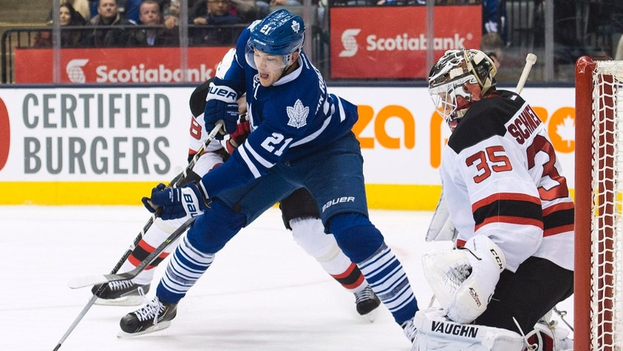 Toronto Maple Leafs forward James van Riemsdyk, left, misses a scoring chance against New Jersey Devils goalie Cory Schneider (35) during second period NHL hockey action in Toronto on Sunday, Jan. 12, 2014. (AP Photo/The Canadian Press, Nathan Denette)