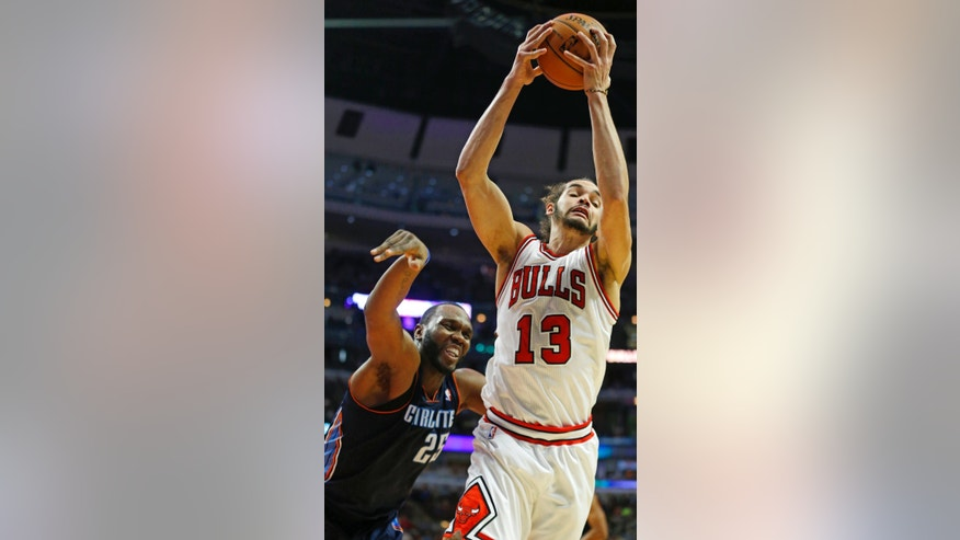 Chicago Bulls center Joakim Noah (13) rebounds the ball away from Charlotte Bobcats center Al Jefferson (25) during the second half of an NBA basketball game in Chicago, Saturday, Jan. 11, 2014. The Bulls won 103-97. (AP Photo/Kamil Krzaczynski)