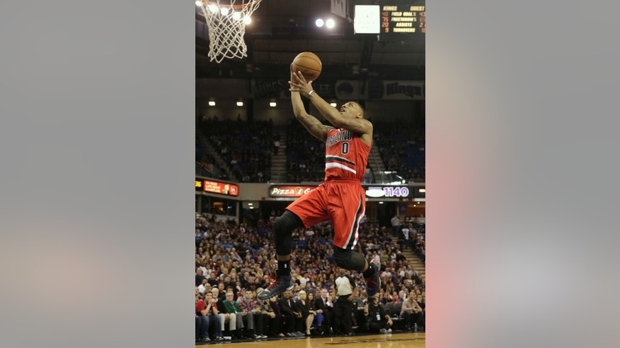 Portland Trail Blazers guard Damian Lillard goes to the basket on a break away layup against the Sacramento Kings during the fourth quarter of an NBA basketball  game in Sacramento, Calif., Tuesday, Jan. 7, 2014.  The Kings won 123-119.(AP Photo/Rich Pedroncelli)