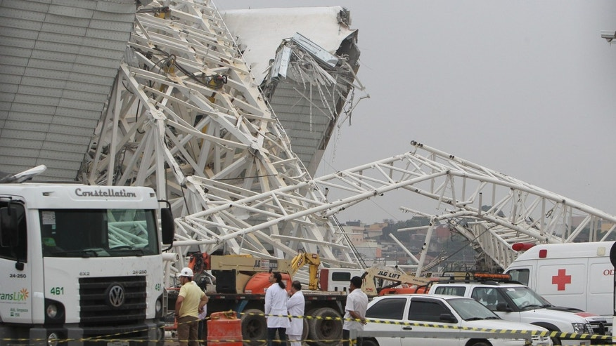 SAO PAULO, BRAZIL - NOVEMBER 27:  Personnel survey the damage at the site of a crane collapse during construction at Itaquerao Stadium on November 27, 2013 in Sao Paulo, Brazil. According to reports, at least two workers were killed in the accident which caused major damage. The stadium is scheduled to host the opening ceremony of the World Cup in 2014. (Photo by Ricardo Bufolin/Getty Images)