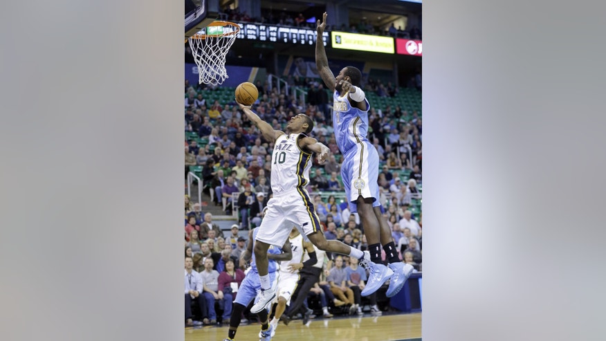 Utah Jazz's Alec Burks (10) goes to the basket as Denver Nuggets' J.J. Hickson (7) defends in the first quarter during an NBA basketball game Monday, Jan. 13, 2014, in Salt Lake City. (AP Photo/Rick Bowmer)