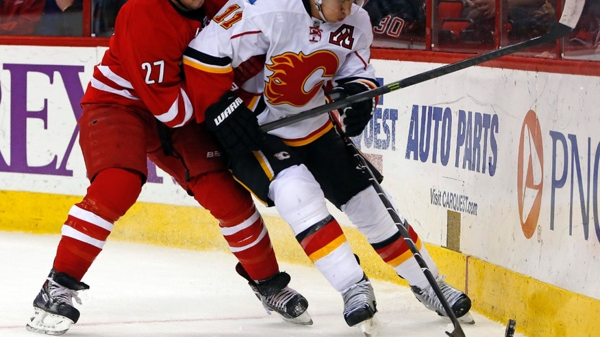 Calgary Flames' Mikael Backlund (11) of Sweden, battles with Carolina Hurricanes' Justin Faulk (27) during the first period of an NHL hockey game in Raleigh, N.C., Monday, Jan. 13, 2014. (AP Photo/Karl B DeBlaker)