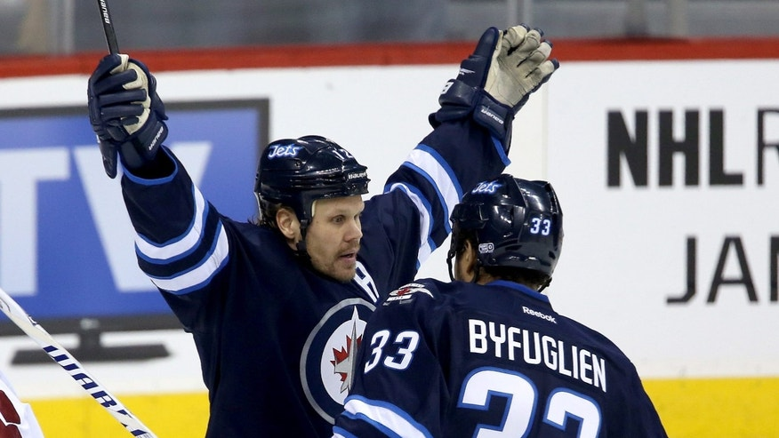 Winnipeg Jets' Olli Jokinen (12) celebrates with Dustin Byfuglien (33) after he scored his 12th goal of the season while playing against the Phoenix Coyotes' during first period NHL hockey action in Winnipeg, Monday, Jan. 13, 2014. (AP Photo/The Canadian Press, Trevor Hagan)