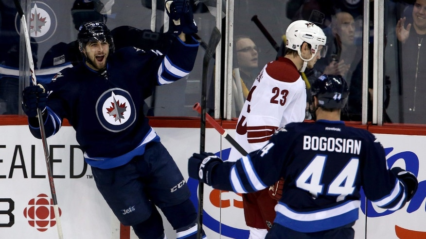 Winnipeg Jets' Eric O'Dell (58) celebrates after scoring with Zach Bogosian (44) as Phoenix Coyotes' Oliver Ekman-Larsson (23) looks on during first period NHL hockey action in Winnipeg, Canada, Monday, Jan. 13, 2014. (AP Photo/The Canadian Press, Trevor Hagan)