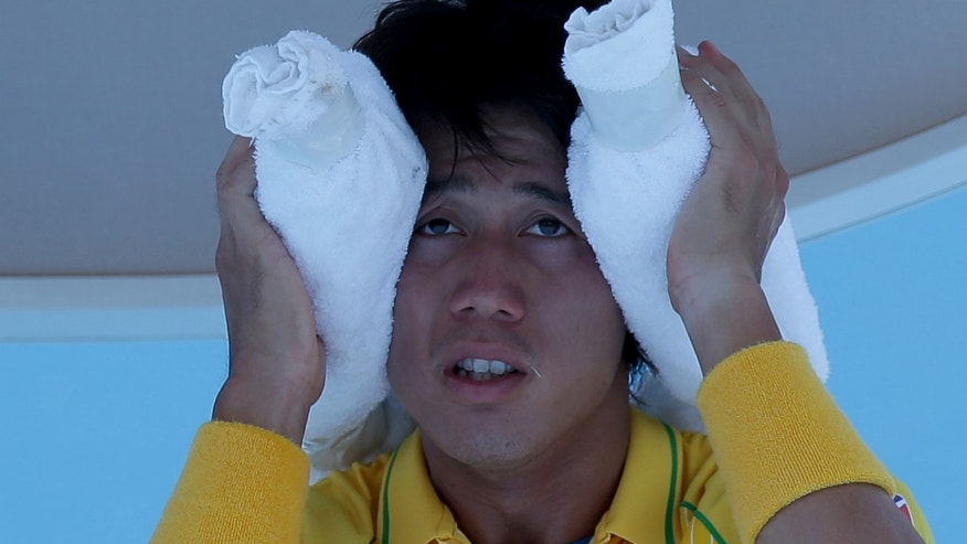Kei Nishikori of Japan wraps an ice pack around his head during a break in his first round match against Marinko Matosevic of Australia at the Australian Open tennis championship in Melbourne, Australia, Tuesday, Jan. 14, 2014.(AP Photo/Aaron Favila)