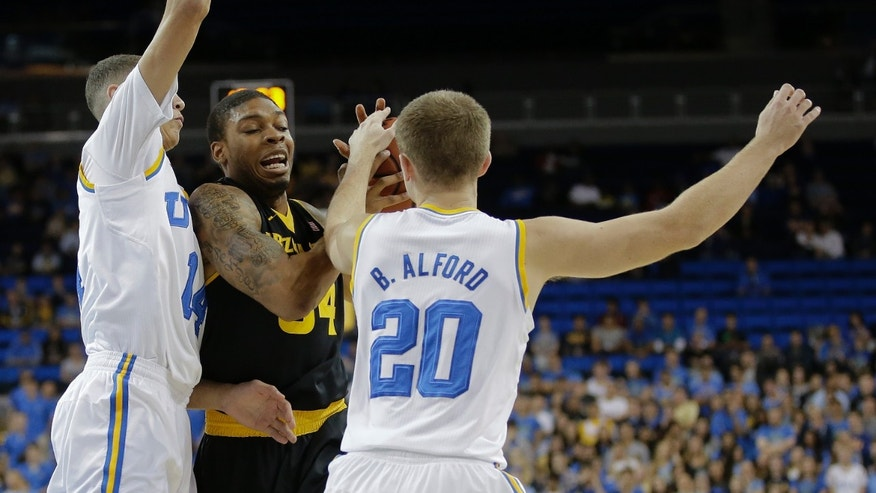 Arizona State guard Jermaine Marshall, center, is trapped by UCLA guard Zach LaVine, left, and guard Bryce Alford during the first half of an NCAA college basketball game in Los Angeles, Sunday, Jan. 12, 2014. (AP Photo/Chris Carlson)
