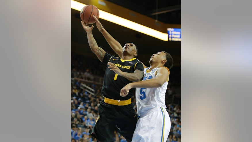 UCLA guard Kyle Anderson, right, blocks a shot by Arizona State guard Jahii Carson during the first half of an NCAA college basketball game in Los Angeles, Sunday, Jan. 12, 2014. (AP Photo/Chris Carlson)