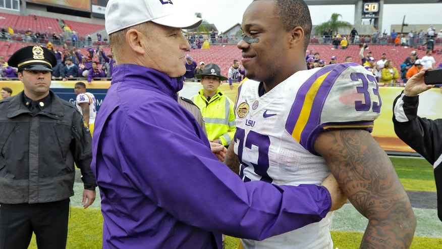 "FILE - In this jan. 1, 2014 file photo, LSU head coach Les Miles, left, congratulates MVP Jeremy Hill (33) after LSU defeated Iowa 21-14 in the Outback Bowl NCAA college football game in Tampa, Fla. LSU leading rusher Jeremy Hill says he's decided to enter the NFL draft. In an announcement made Monday, jan. 13, 2014,  on a social media website, Hill says he's grateful to LSU fans, friends, coaches and family and his decision was ""very difficult."" (AP Photo/Chris O'Meara, File)"