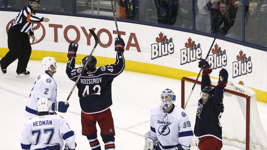 Columbus Blue Jackets' Mark Letestu (55), right, and Artem Anisimov (42), of Russia, celebrate the winning goal by Jack Johnson as Tampa Bay Lightnings goalie Anders Lindback (39), of Sweden, kneels on the ice during the third period of an NHL hockey game, Monday, Jan. 13, 2014, in Columbus, Ohio. (AP Photo/Mike Munden)