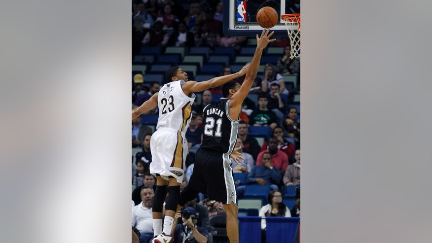 San Antonio Spurs power forward Tim Duncan (21) goes to the basket against New Orleans Pelicans power forward Anthony Davis (23) in the first half of an NBA basketball game in New Orleans, Monday, Jan. 13, 2014. (AP Photo/Gerald Herbert)
