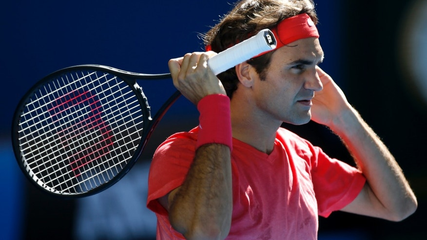 Roger Federer of Switzerland waits to receive serve during a practice session ahead of the Australian Open tennis championship in Melbourne, Australia, Sunday, Jan. 12, 2014.(AP Photo/Eugene Hoshiko)