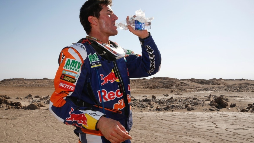 KTM rider Marc Coma of Spain drinks water at the first check point during the ninth stage of the Dakar Rally between the cities of Calama and Iquique, Chile, Tuesday, Jan. 14, 2014. (AP Photo/Victor R. Caivano)