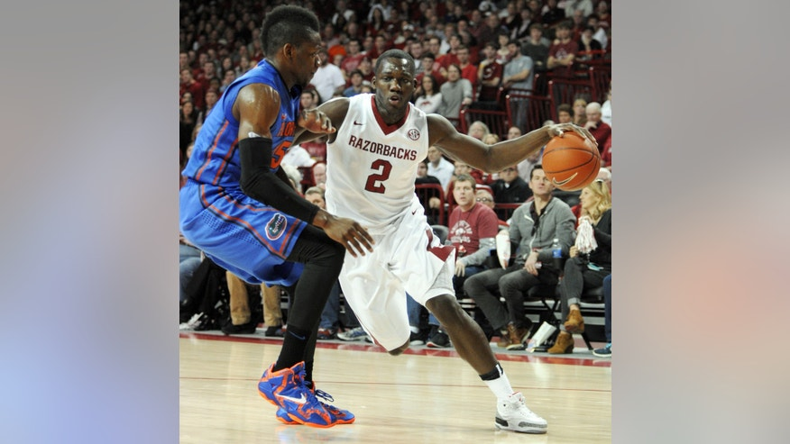 Arkansas forward Alandise Harris (2) drives past Florida forward Will Yeguete, of France, during an NCAA college basketball game in Fayetteville, Ark., Saturday, Jan. 11, 2014. Florida won 84-82. (AP Photo/David Quinn)