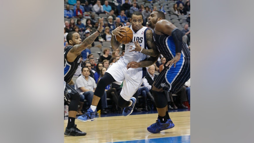 Dallas Mavericks shooting guard Monta Ellis, center, drives between Orlando forward Glen Davis and point guard Jameer Nelson during the second half of an NBA basketball game, Monday, Jan. 13, 2014, in Dallas. The Mavericks won 107-88.  (AP Photo/LM Otero)