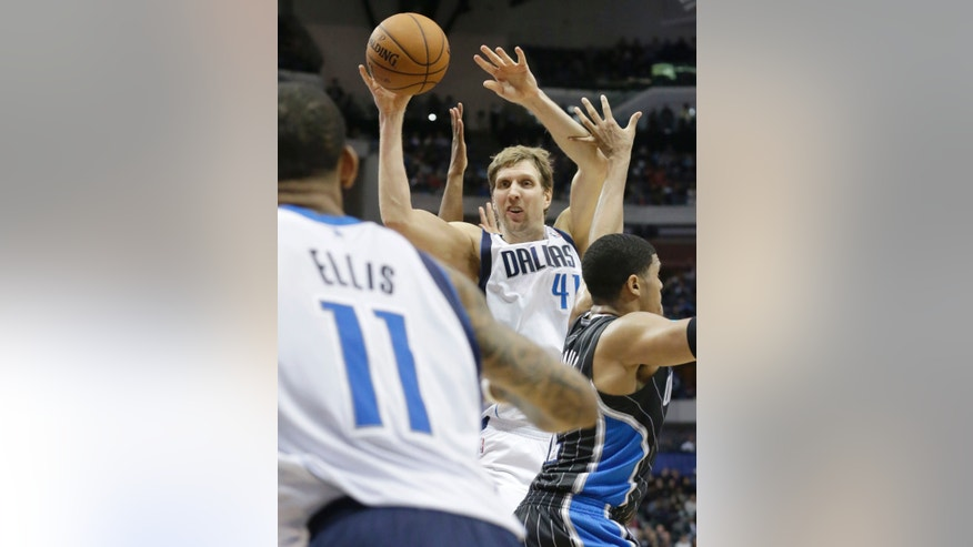 Dallas Mavericks power forward Dirk Nowitzki (41), of Germany, passes to teammate Monta Ellis (11) against Orlando Magic small forward Tobias Harris (12) during the first half of an NBA basketball game, Monday, Jan. 13, 2014, in Dallas. (AP Photo/LM Otero)