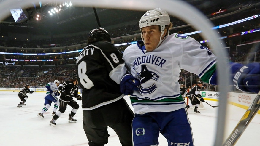 Vancouver Canucks ' Dale Weise, right, and Los Angeles Kings defenseman Drew Doughty (8) tangle in the first period of an NHL hockey game in Los Angeles, Monday, Jan. 13, 2014.  (AP Photo/Reed Saxon)