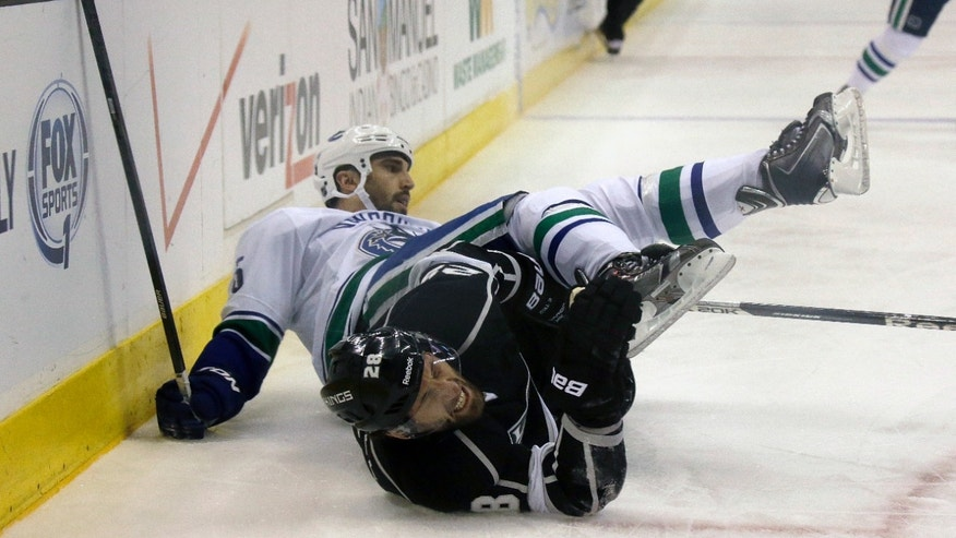 Vancouver Canucks defenseman Jason Garrison, left, and Los Angeles Kings center Jarret Stoll (28) collide in the first period of an NHL hockey game in Los Angeles, Monday, Jan. 13, 2014.  (AP Photo/Reed Saxon)